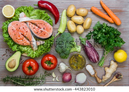 Left fresh salmon fillets on the lettuce near summer season vegetables, herb, spices and olive on wood background. Salmon fillets and summer vegetable ingredients, spices. Horizontal. Top view. - stock photo