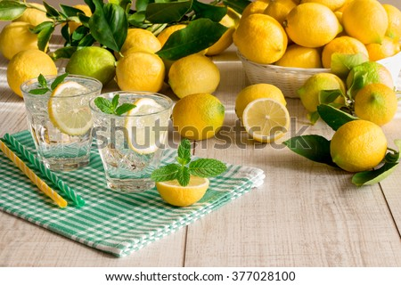 Left 2 glasses of soda water with a slice of lemon, mint leaves, ice cubes on green checkered napkin behind lemons scattered and in a basket on a light wood background. Lemon soda water. Horizontal.  - stock photo