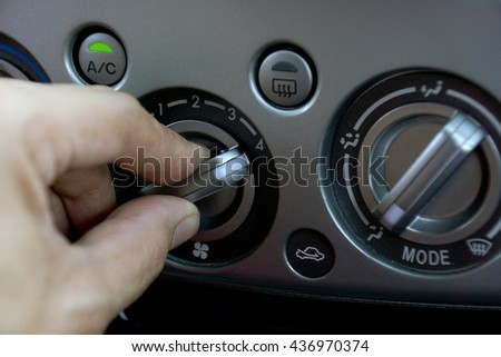 Left hand adjusting a fan level control knob of the car's air conditioning system.