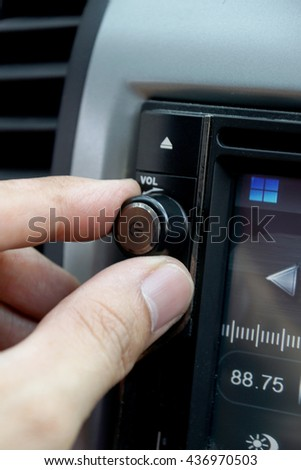 Left hand adjusting a volume control knob of the car's audio system.