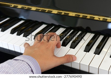 Left hand of a piano player - stock photo