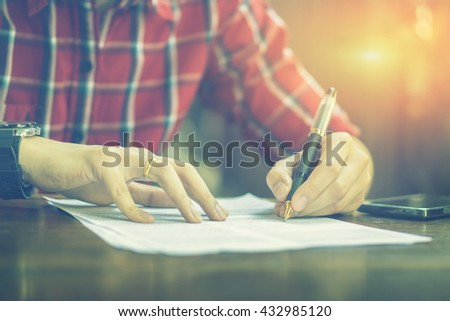 left hand Writing,Businessperson Signing Contract,Man writing paper at the desk, man writing with pen,register a marriage,divorce,man Signing, Contract, Form in office ,vintage color ,selective focus. - stock photo