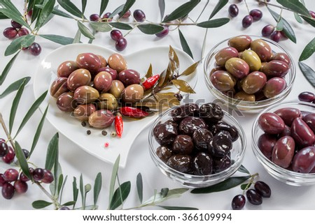 Left in a white heart shape plate green olives, right 3 glass bowls with of olives green, black, sun-dried framed by olive tree branches on a white background. 3 types of greek olives. Horizontal. - stock photo