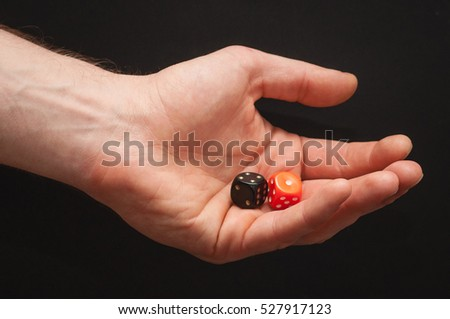 Left male arm holding black and white dice showing four and one on a isolated seamless abstract black background.