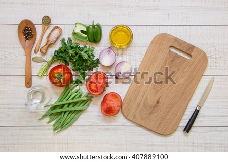 Left vegetables ready to cook tomatoes, peppers, green beans, onions, parsley, spices, water jar, right clean board and knife on light wood background. Vegetables ingredients. Horizontal. Top view. - stock photo