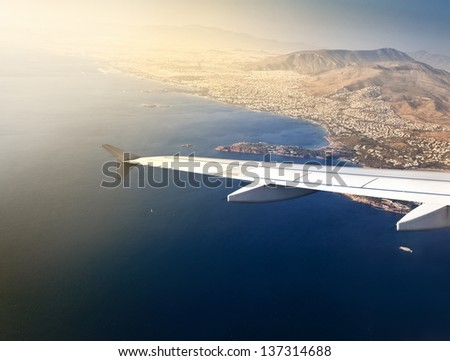 Left wing of an aircraft just before landing in Athens (Greece) - stock photo