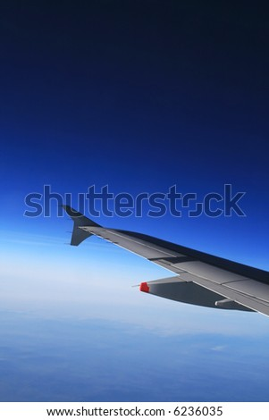 Left wing of the aircraft over clear and cloudless sky. Free space for text above the wing.
