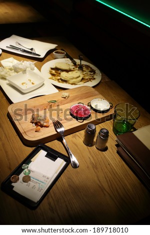 Leftover food and the bill on a table at czech restaurant - stock photo