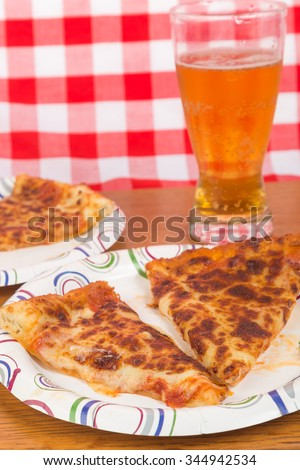 Leftover pizza reheated and served on paper plates with cold beer.  Vertical format. - stock photo