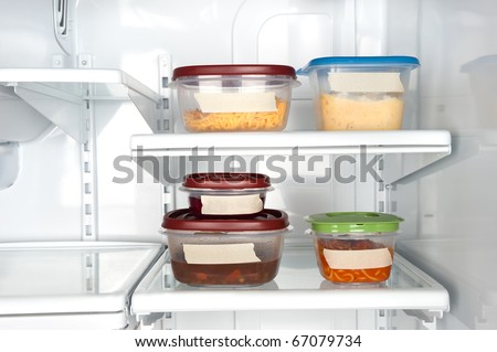 Leftovers in a refrigerator with blank tape for copy. - stock photo