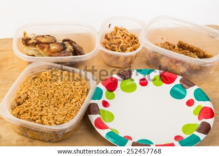 Leftovers in plastic bowls on cutting board with paper plates. - stock photo