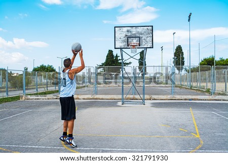 lefty basketball player shooting in a playground - stock photo