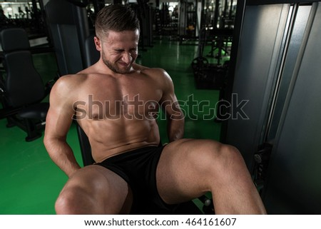 Leg Exercises Close Up -  Man struggling Doing Leg With Machine In Gym