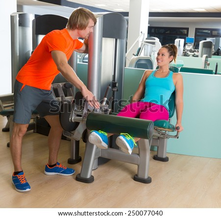 Leg extension exercise woman at gym indoor workout with personal trainer blond man