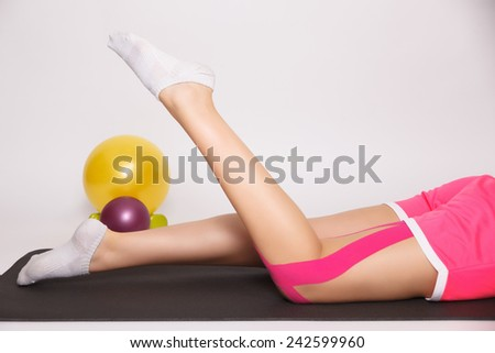 Leg injury treated with kinesiology tape - stock photo