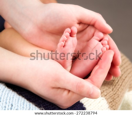 leg newborn little baby in the mother's hands