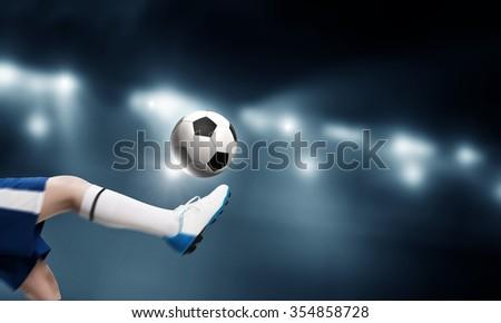 Leg of kid boy in blue uniform on soccer stadium kicking ball - stock photo