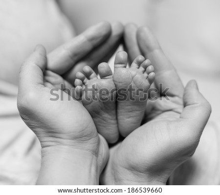 Leg of the newborn in the hands of father. Black-and-white photo - stock photo