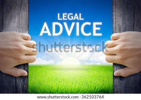Legal Advice. Hand opening an old wooden door and found Legal Advice word floating over green field and bright blue Sky Sunrise. - stock photo