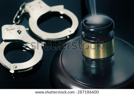 Legal judgement handed down - cuffs and hammer - stock photo