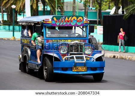 LEGAZPI, PHILIPPINES - MARCH 17, 2014: Jeepneys passing, Filipino inexpensive bus service. Jeepneys are the most popular means of public transportation in the Philippines. - stock photo