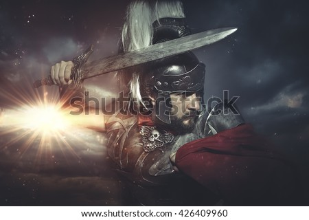 Legionary warrior helmet, armor and red cape on a battlefield, conflict and struggle in the Roman Empire - stock photo