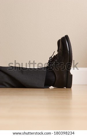 Legs and feet of lying passed out business man - stock photo