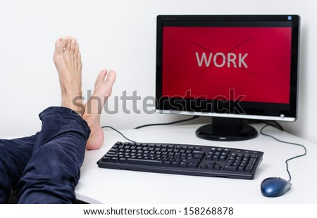 legs and feet without shoes on desk with red screen - stock photo