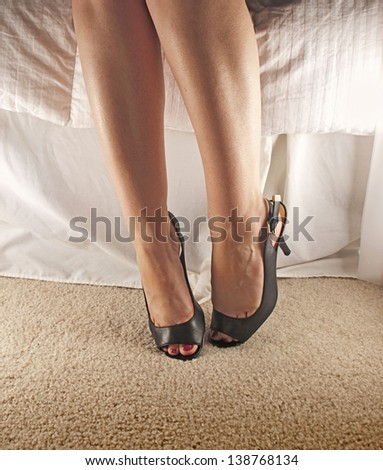 Legs and heels sitting on a bed - stock photo