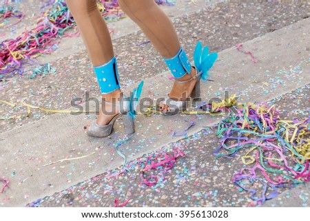 Legs and shoes girls at the carnival. Scattered confetti. - stock photo