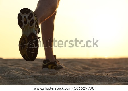 Legs and shoes of a man running at sunset with the horizon in the background - stock photo