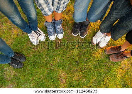 Legs and sneakers of teenage boys and girls standing in half circle on the grass.
