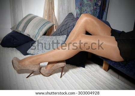 Legs covered from a pair of pantyhose with high heels shoes - stock photo