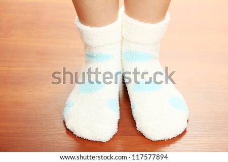 Legs female in socks with polka dots on laminate floor - stock photo