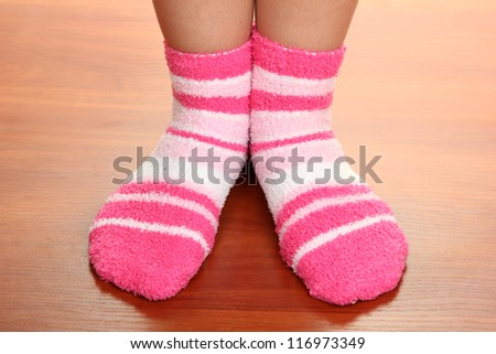 Legs female in striped socks on laminate floor