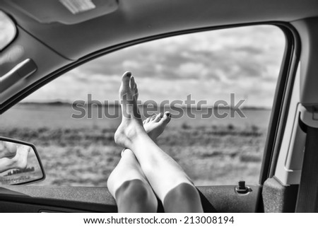 Legs hanging out vehicle window - stock photo