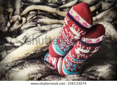 legs in Christmas socks under a blanket of fur. toning image - stock photo