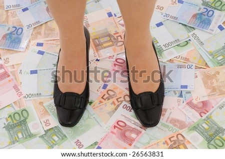 Legs in elegant shoes on euro banknotes (money under control and security concepts) - stock photo