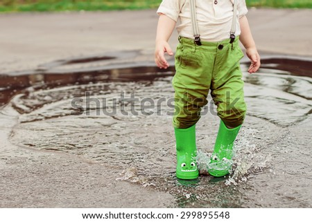 Legs in green rubber boots with dragon faces splashing through the puddles. Image with selective focus - stock photo