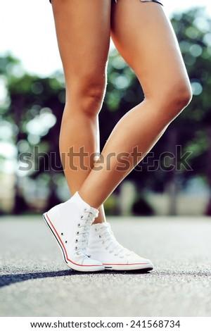 Legs in sneakers - stock photo
