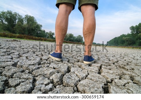 Legs in sneakers of man standing on cracked ground during summer drought. - stock photo