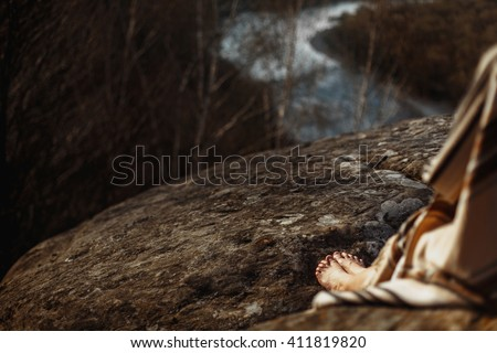 legs native indian american woman with warrior shaman make up sitting on rocks on background of woods and river - stock photo
