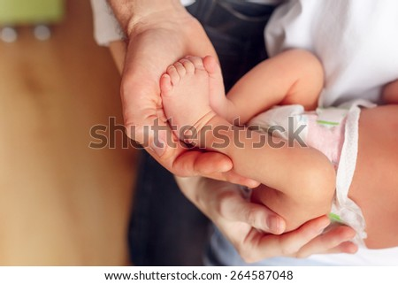 legs newborn baby in hands of parents - stock photo