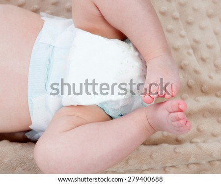 Legs of a baby with diaper on a blanket - stock photo