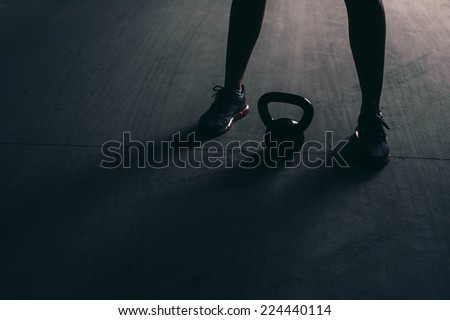 Legs of a bodybuilder with a kettlebell lying between them on a concrete floor - stock photo