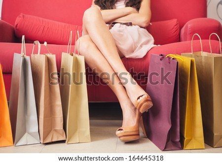 Legs of a Caucasian woman surrounded by many shopping bags.