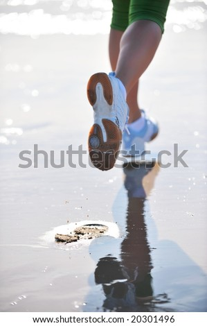 legs of a girl jogging on the beach - stock photo