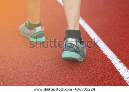 Legs of a man walk around the track on a sunny spring day