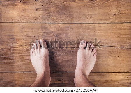 Legs of a runner on a wooden floor background - stock photo