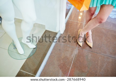 Legs of a shopper standing on the floor and those of mannequin in the shop window - stock photo